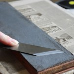 The back of the paring knife is kept flat when sharpening or using the strop